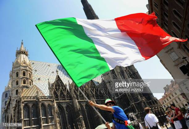 Supporter of the Italian national football team waves an Italian flag in front of St. Stephen's Cathedral in central Vienna on June 22 hours before...
