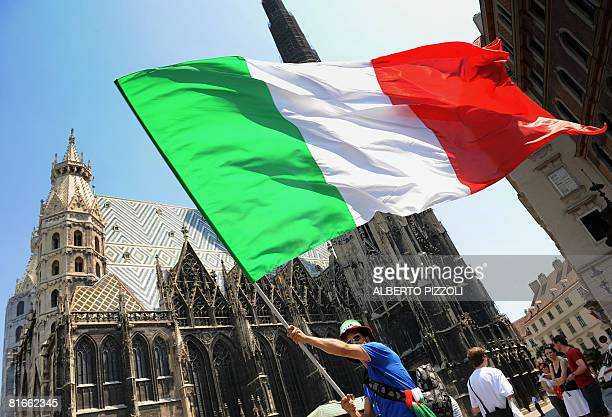 A supporter of the Italian national football team waves an Italian flag in front of St Stephen's Cathedral in central Vienna on June 22 hours before...