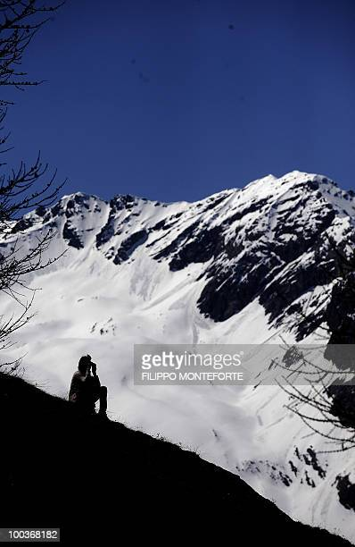 Supporter of the Italian soccer team follows the training session with binoculars from a hill top in Sestriere on May 24, 2010. The italian team is...
