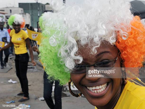 A supporter of the Ivorian national football team wearing a wig with the country's national colors smiles on June 10 2010 during a street parade in...
