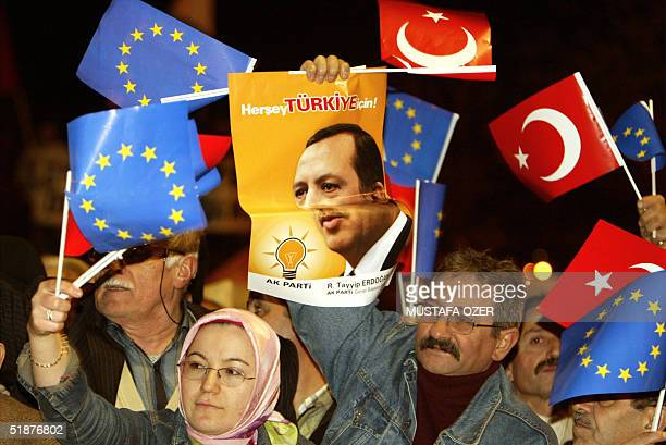 Supporter of the Justice and Development Party holds Erdogan's poster as others waves national and EU flags as Turkish Prime Minister Recep Tayyip...