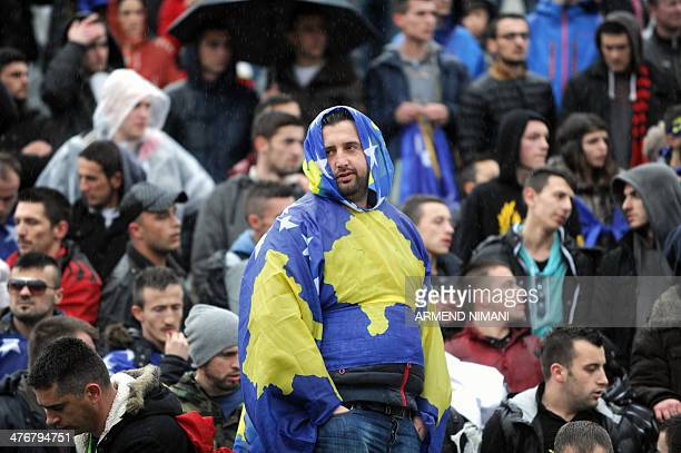 A supporter of the Kosovo's national football team wrapped in a Kosovo flag stands in the stands during the friendly football match between Kosovo...