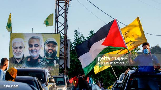 Supporter of the Lebanese Shiite movement Hezbollah waves Palestinian and Hezbollah flags while riding in a vehicle past a billboard showing the...