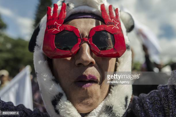 A supporter of the 'Libertad y Refundacion' party with her sunglasses reading 'LIBRE' takes part in a protest against current president Juan Orlando...