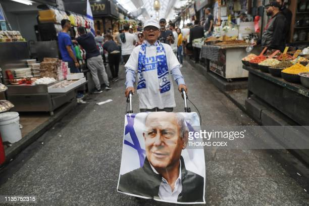 Supporter of the Likud party pushes a trolley covered with a poster bearing a portrait of Israeli Prime Minister Benjamin Netanyahu along an alley of...