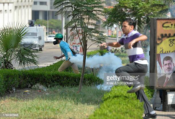 Supporter of the Muslim Brotherhood and Egypt's ousted president Mohamed Morsi carries a tear gas canister fired by riot police during clashes near...