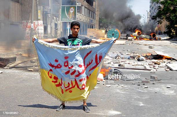 """Supporter of the Muslim Brotherhood and Egypt's ousted president Mohamed Morsi holds a banner reading in Arabic: """"Alexandria is against the coup"""" as..."""