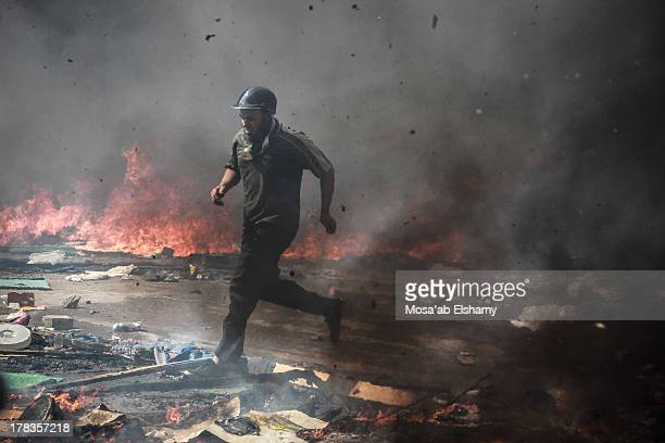 Supporter of the Muslim Brotherhood and Egypt's ousted president Mohamed Morsi is seen during clashes with police in Cairo on August 14 as security...