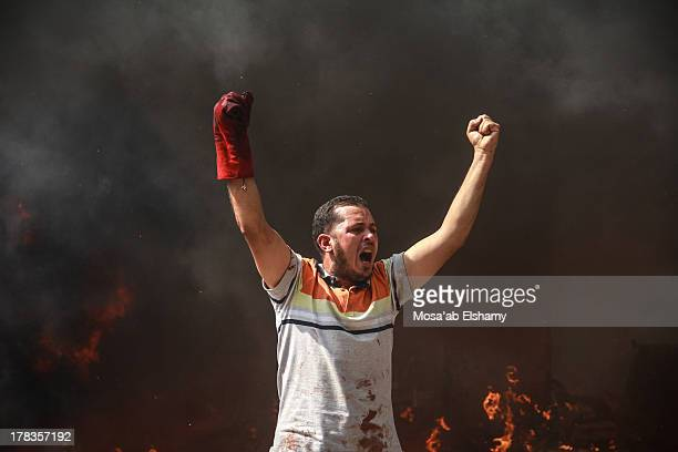Supporter of the Muslim Brotherhood and Egypt's ousted president Mohamed Morsi gestures during clashes with police in Cairo on August 14 as security...