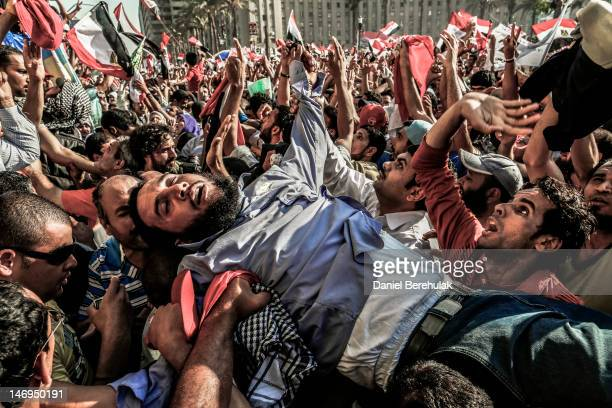 Supporter of the Muslim Brotherhood overcome by emotion is carried onto the stage as Egyptians celebrate the election of their new president Mohamed...