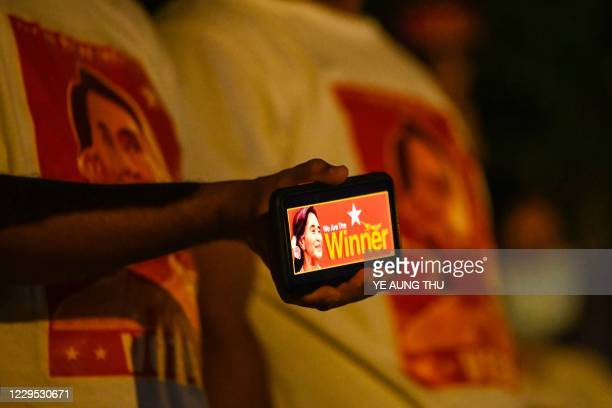 Supporter of the National League for Democracy party holds a mobile phone with an image of Aung San Suu Kyi in front of the party's headquarters in...