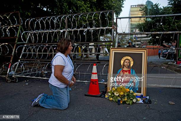 A supporter of the National Republican Alliance's presidential candidate Norman Quijano prays next to a framed image of the Sacred heart of Jesus...