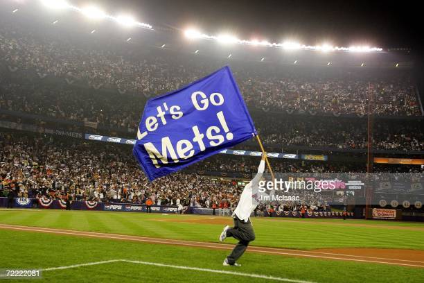 """Supporter of the New York Mets runs on the field with a flag that reads """"Lets Go Mets!"""" before their game against the St. Louis Cardinals during game..."""