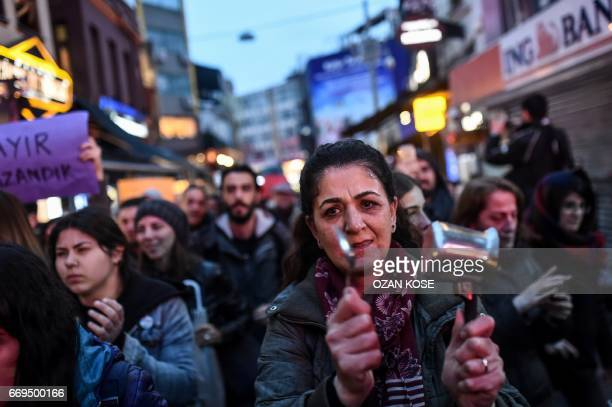 """Supporter of the """"No"""" hits with a spoon the back of a pan as she takes part in a gather at the Besiktas district in Istanbul on April 17, 2017 to..."""