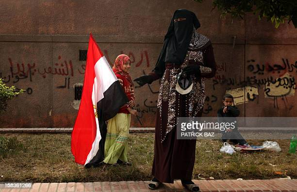 A supporter of the opposition against Egyptian President Mohamed Morsi stands with her children one of whom is waving the Egyptian flag outside the...