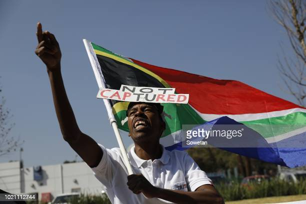 A supporter of the Organisation Undoing Tax Abuse holds a South African flag while picketing outside Raymond Zondos judicial commission of inquiry...