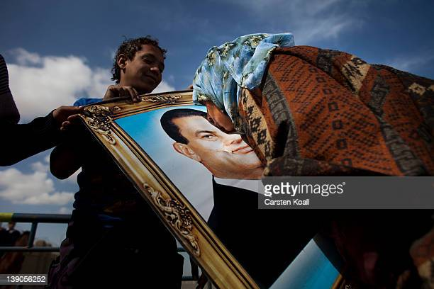 A supporter of the ousted Egyptian president Hosni Mubarak kisses his picture as she demonstrates outside the police academy as Mubarak's trial...