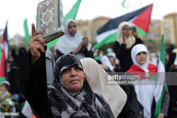 A supporter of the Palestinian Islamic group Hamas shows a Koran Islam's holy book during a festival of the International Association of Muslim...