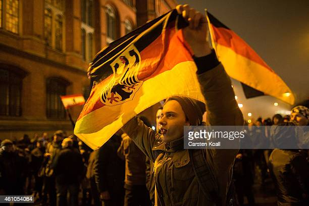 A supporter of the Pegida movement holds a flag while supporters gather for a march in their first Berlin demonstration which they have dubbed...