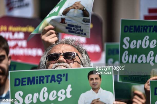 A supporter of the Peoples' Democratic Party looks up as he holds a placard reading 'Free Demirtas' in front of Istanbul's Courthouse on May 21 to...