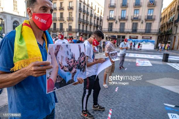 Supporter of the Popular Rif Movement wearing a mask is seen showing a placard of Rif leader and activist Nasser Zefzafi during the rally....