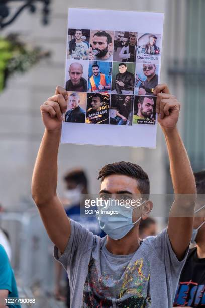 Supporter of the Popular Rif Movement wearing a mask is seen showing a placard with the portraits of various Rife political prisoners during the...