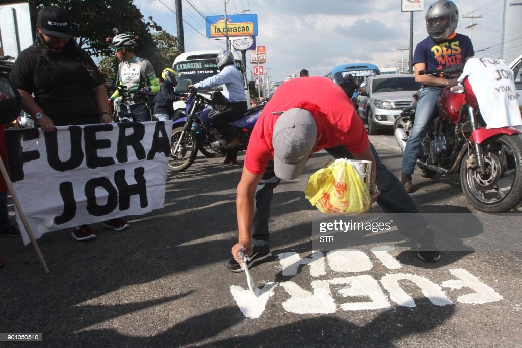 A supporter of the presidential candidate for the Honduran Opposition Alliance Against the Dictatorship, Salvador Nasralla, paints 'JOH Get Out!' (for President Juan Orlando Hernandez, JOH) on the street during a protest in Tegucigalpa on January 12, 2018. Tens of thousands of people protested Friday in the Honduran capital against the reelection of President Juan Orlando Hernandez, as the January 27 start of his second term approaches. /