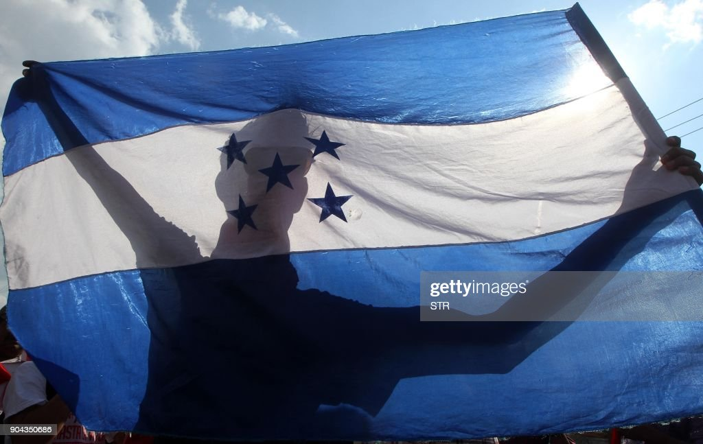 A supporter of the presidential candidate for the Honduran Opposition Alliance Against the Dictatorship, Salvador Nasralla, holds a Honduran flag during a protest in Tegucigalpa on January 12, 2018. Tens of thousands of people protested Friday in the Honduran capital against the reelection of President Juan Orlando Hernandez, as the January 27 start of his second term approaches. /