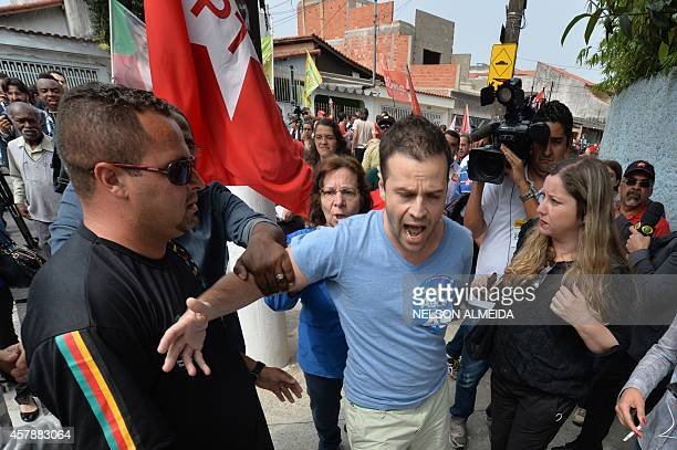 Supporter of the presidential candidate Social Democrat Aecio Neves who shouts slogans is contained as the Brazilian former president Luiz Inacio...