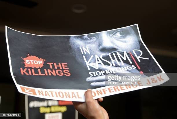 A supporter of the proIndian political party National Confrence holds a placard at a protest against recent killings in the Kashmir conflict in...