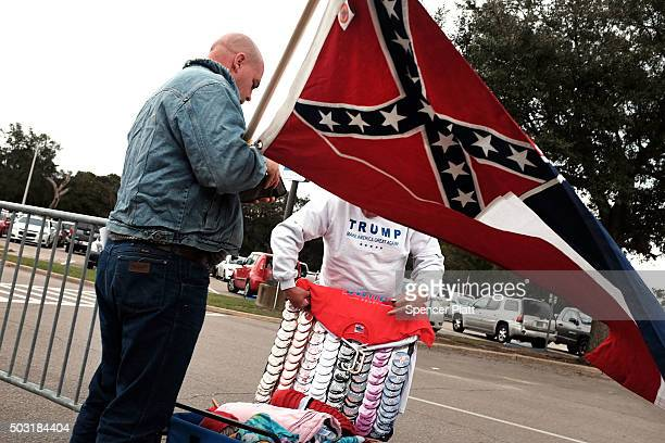 A supporter of the Republican presidential frontrunner Donald Trump purchases Trump merchandise while waiting to hear him speak at the Mississippi...
