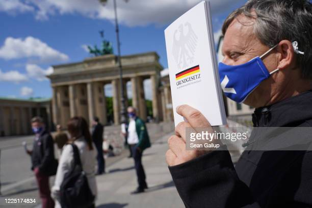 A supporter of the rightwing Alternative for Germany political party holds a copy of Germany's Basic Law its constitution as he wears a protective...