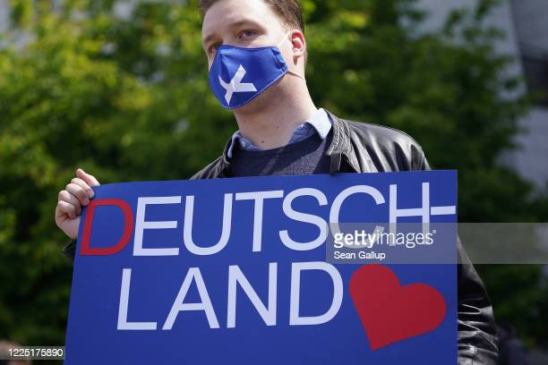A supporter of the rightwing Alternative for Germany political party wears a protective face mask and holds a sign that reads Germany at an AfD...