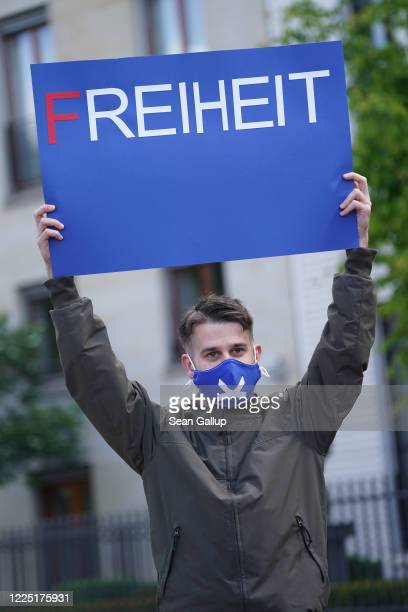 A supporter of the rightwing Alternative for Germany political party wears a protective face mask and holds a sign that reads freedom at an AfD...