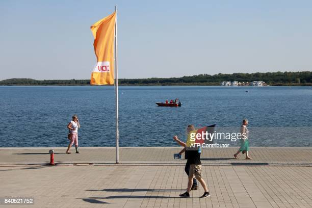 A supporter of the rightwing populist Alternative for Germany carries a German flag as he walks past a CDU flag prior to an election campaign rally...