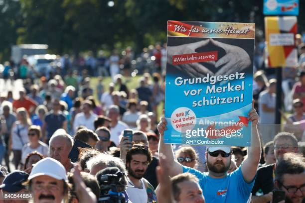 A supporter of the rightwing populist Alternative for Germany holds up a placard which reads Protect the constitution from Merkel as German...