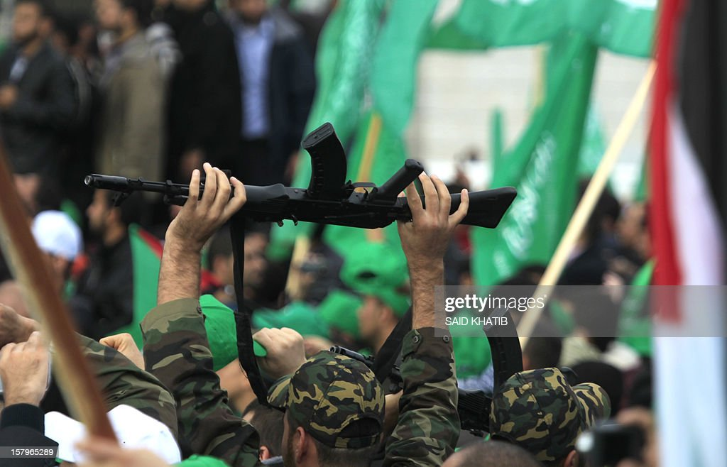 A supporter of the ruling Hamas movement holds up his rifle during a rally to mark the 25th anniversary of the founding of the Islamist movement, in Gaza City on December 8, 2012. Hamas leader in exile Khaled Meshaal made his first visit to Gaza, timed to coincide with the 25th anniversary of the Islamist movement's founding.