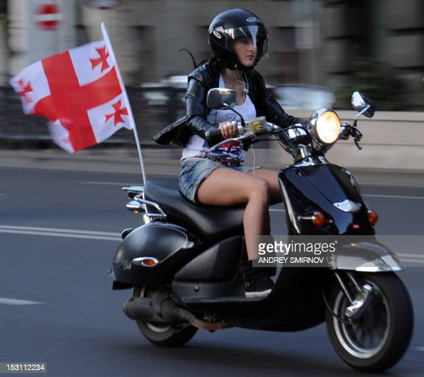 A supporter of the ruling United National Movement party rides a scooter in Tbilisi on September 30 2012 on the eve of parliamentary elections The...