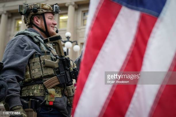 A supporter of the Second Amendment carries a semiautomatic rifle during a rally in support of the Second Amendment at the State Capitol on January...