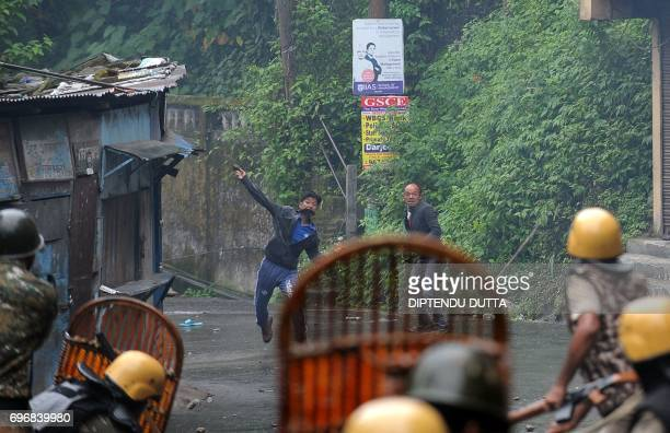A supporter of the separatist Gorkha Janmukti Morcha group throws a rock during clashes with Indian security forces in Darjeeling on June 17 2017...
