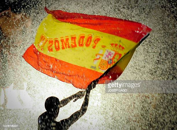 A supporter of the Spanish team waves a Spanish flag in celebration after the World Cup final football match Spain against Netherlands on July 11...