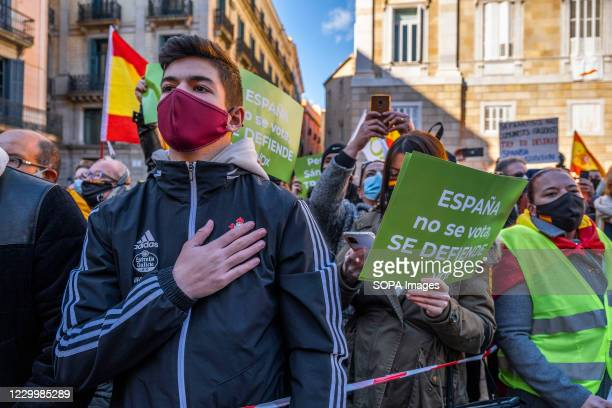 Supporter of the ultra-right party VOX wearing a face mask is seen singing the Spanish national anthem in Plaza de Sant Jaume. On the occasion of the...