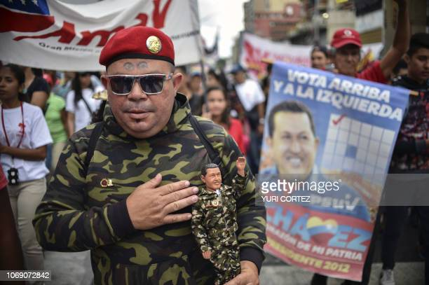 A supporter of the United Socialist Party of Venezuela holds a doll of late Venezuelan president Hugo Chavez while taking part in a rally to...