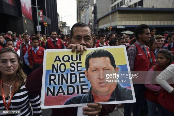 A supporter of the United Socialist Party of Venezuela holds a placard with the image of late Venezuelan president Hugo Chavez and a legend reading...
