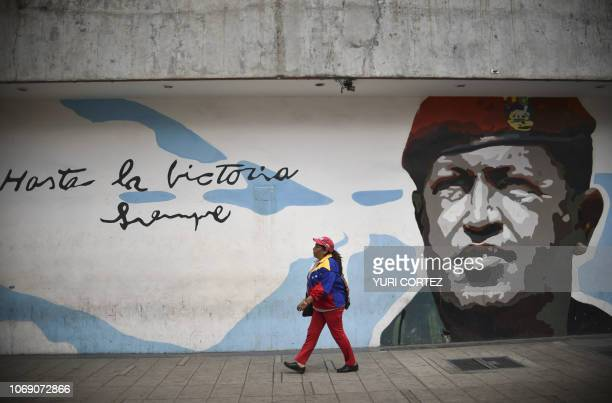 TOPSHOT A supporter of the United Socialist Party of Venezuela walks past a grafitti depicting late Venezuelan president Hugo Chavez during a rally...