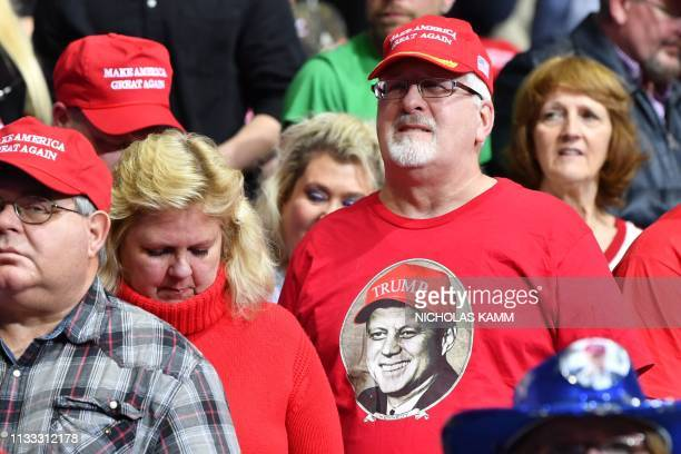 A supporter of the US president wears a tshirt featuring a portrait of former US President John F Kennedy wearing a Trump hat as he attends a...