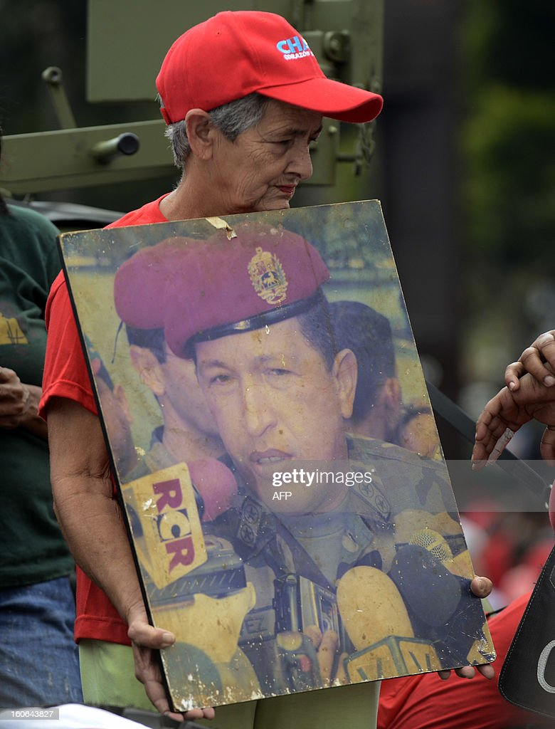 A supporter of the Venezuelan President Hugo Chavez displays a poster of the leader during a march to conmemorate the 1992 failed coup led by Chavez, who was an army lieutenant colonel, against then president Carlos Andres Perez, in Caracas, on February 4, 2013. Ailing President Hugo Chavez, who had cancer surgery in December, is doing much better and recovering, Cuban leader Fidel Castro said in remarks published Monday. AFP PHOTO/Leo RAMIREZ