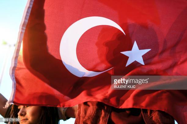 A supporter of the 'yes' waves a Turkish national flag during a rally in front of Turkish president residence at Sariyer district in Istanbul on...