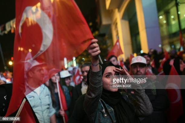 A supporter of the 'yes' waves a Turkish national flag during a rally near the headquarters of the conservative Justice and Development Party on...