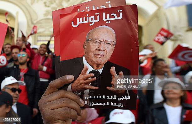 Supporter of Tunisian Presidential candidate Beji Caid Essebsi holds up a portrait of him during a campaign rally on Bourguiba avenue in the capital,...